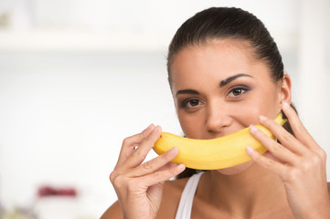 creative portrait of woman holding yellow banana in her hand.