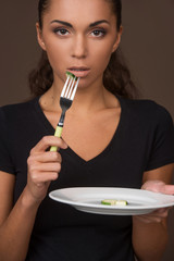 Portrait of pretty young girl eating cucambers.