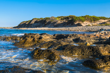 Costline with dunes and rocks in sun light