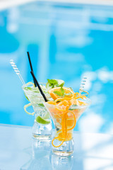 Orange and lime Mojito by the swimming pool