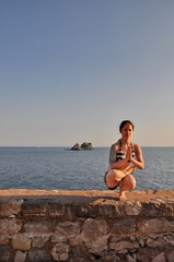 Young woman doing yoga pose at the sea