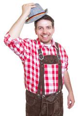 Lachender Mann in Lederhose grüsst mit Hut