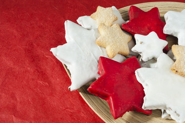 Christmas cookies on wooden plate o red table.