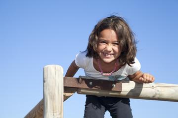 Niña sonriendo subida a una valla