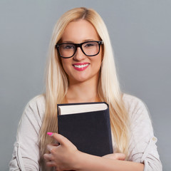 Portrait of a woman wearing glasses and holding a book..