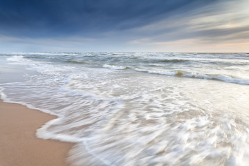 North sea waves on sand beach