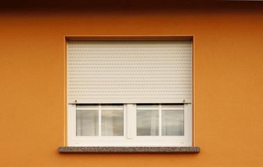 Modernes Kunststofffenster mit halb geschlossenem Rollladen