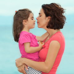 Portrait of mother and daughter kissing by the seaside