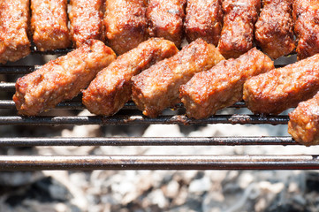 minced meat rolls on grill (traditional Romanian food) mici