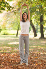 Young woman exercising in a park on a warm autumn day.