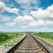 railroad to horizon in green landscape and cloudy sky