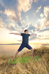 Young man practicing yoga in nature at sunset.