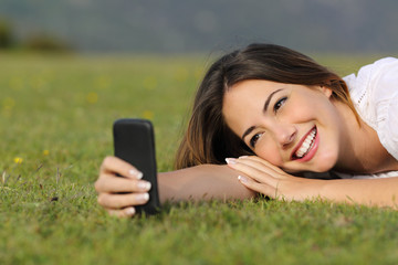 Pretty girl smiling using a smart phone lying on the grass