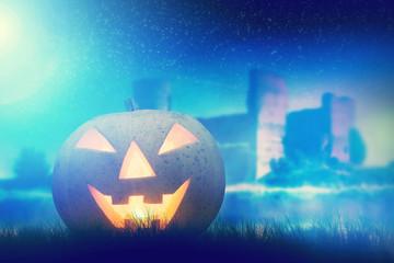 Halloween pumpkin glowing in dark night with gothic castle