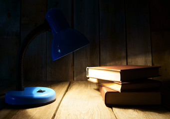 The fixture and the books. On wooden background.