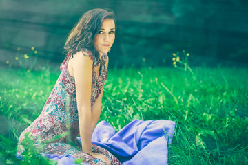 Beautiful young woman sitting in a green meadow
