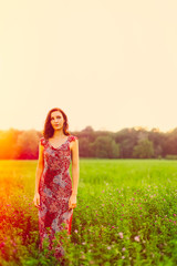 Stylish young woman standing in a morning meadow