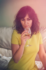 Thoughtful young woman smelling a glass of wine, the morning aft