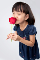 Happy little girl smelling a rose