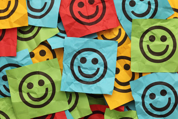 Crumpled adhesive notes with smiling faces
