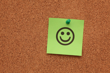 Green paper with smiling face on corkboard
