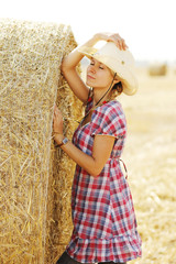 young girl near haystacks in cowboy hat