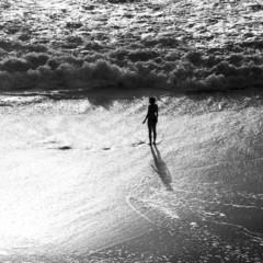 silhouette of girl on beach in breaking waves