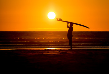 silhouetted man with surfboard in sunset at beach