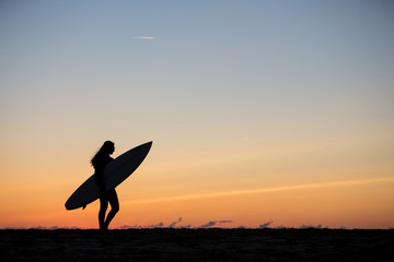 silhouetted girl with surfboard in sunset at beach