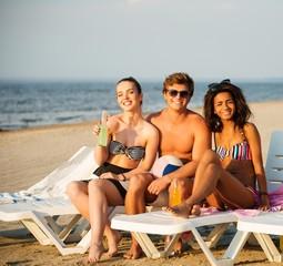 Multi ethnic friends sunbathing on a beach