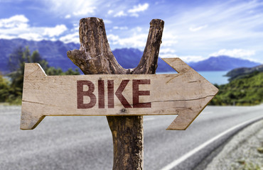 Bike wooden sign with a street background