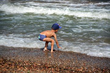 niño jugando en la orilla de mar