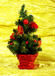 Little decorated christmas tree on golden background with gifts