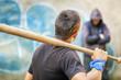 Aggressive teenager with a baseball bat against man at outdoor