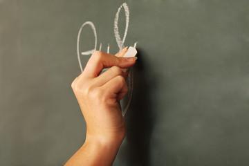 Mit Kreide an die Tafel schreiben
