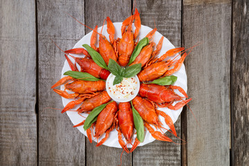 Plate with red boiled crayfish on a wooden table, top view