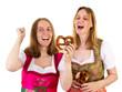 Women in dirndl eating delicious pretzel