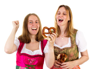 Women in dirndl eating delicious pretzel