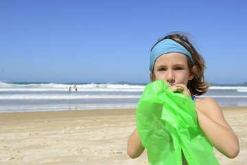 Child inflating inflatable swim ring on the beach