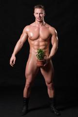 bodybuilder holding a flower in a pot