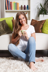 Beautiful young woman drinking a cup of tea in the living room