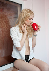 Portrait of a young, blonde woman, holding a mug with her hands
