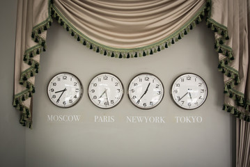 clocks on a wall with time zone of different country