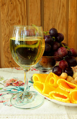 Glass of dry wine, cheese and a bunch of ripe grapes.