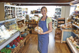 Owner Of Delicatessen Standing In Shop Holding Loaf Of Bread
