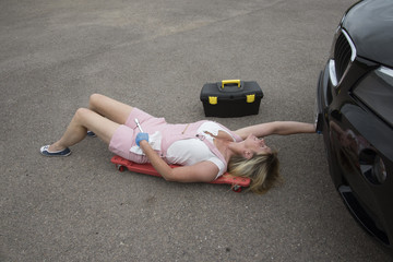 Motor mechanic laying on a crawler to gain access under a car