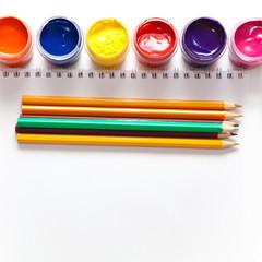 Краски и цветные карандаши на белом фоне