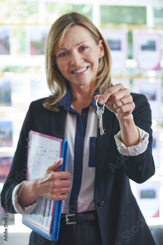 canvas print picture Estate Agent In Office Holding Keys To Property