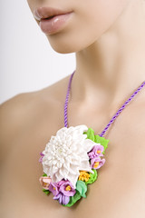 Fashion studio shot of beautiful woman with a floral necklace ar