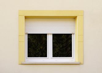 Modernes Fenster mit Rollladen und gelber Fenstereinfassung